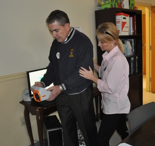 Lion Cyd McDowell instructs Lion John Hagan on the using the vision screening technology